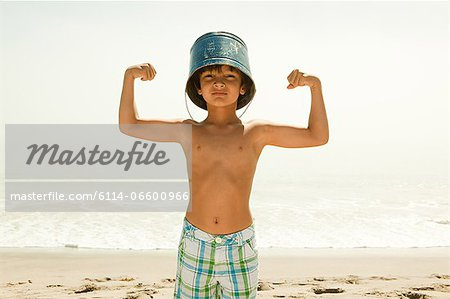 Boy with bucket on head, flexing muscles Stock Photo - Premium Royalty-Free, Image code: 6114-06600966