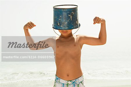Boy with bucket on head, flexing muscles Stock Photo - Premium Royalty-Free, Image code: 6114-06600967