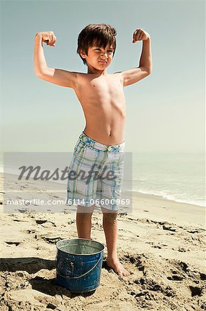 Boy standing on beach flexing muscles Stock Photo - Premium Royalty-Free, Image code: 6114-06600969