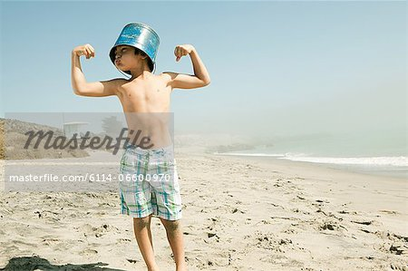 Boy with bucket on head, flexing muscles Stock Photo - Premium Royalty-Free, Image code: 6114-06600970