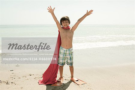 Boy wearing flippers and red cape on beach Stock Photo - Premium Royalty-Free, Image code: 6114-06600974