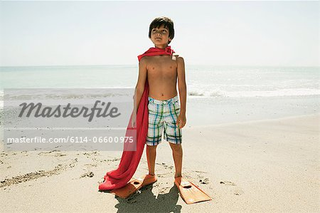 Boy wearing flippers and red cape on beach Stock Photo - Premium Royalty-Free, Image code: 6114-06600975
