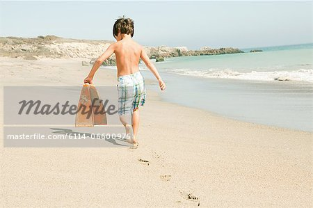 Boy on beach carrying swimming flippers Stock Photo - Premium Royalty-Free, Image code: 6114-06600976