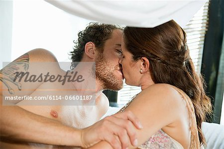 Mid adult couple kissing on vacation Stock Photo - Premium Royalty-Free, Image code: 6114-06601187