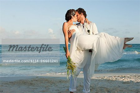 Bride and groom kissing on beach Stock Photo - Premium Royalty-Free, Image code: 6114-06601241