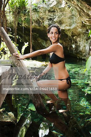 Young woman one wooden ladder, Grande Cenote, Quintana Roo, Tulum, Mexico Stock Photo - Premium Royalty-Free, Image code: 6114-06601650