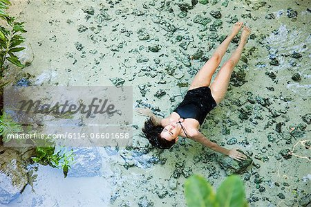 Young woman floating in lagoon, Grande Cenote, Quintana Roo, Tulum, Mexico Stock Photo - Premium Royalty-Free, Image code: 6114-06601658