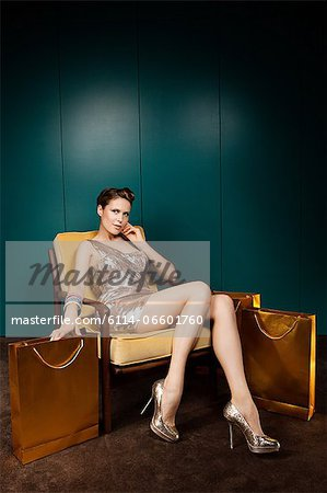 Young woman sitting on chair with shopping bags Stock Photo - Premium Royalty-Free, Image code: 6114-06601760