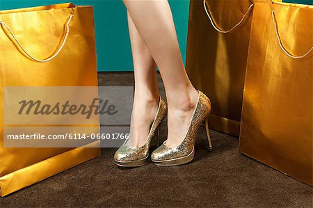 Young woman wearing gold stilettos with shopping bags Stock Photo - Premium Royalty-Free, Image code: 6114-06601766