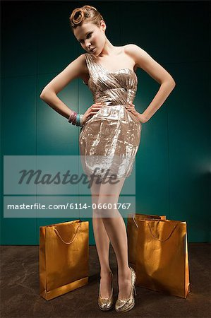 Young woman wearing gold dress with shopping bags, portrait Stock Photo - Premium Royalty-Free, Image code: 6114-06601767