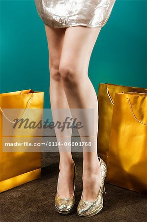 Young woman wearing gold stilettos with shopping bags Stock Photo - Premium Royalty-Free, Image code: 6114-06601768