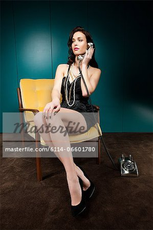 Young woman using vintage telephone Stock Photo - Premium Royalty-Free, Image code: 6114-06601780