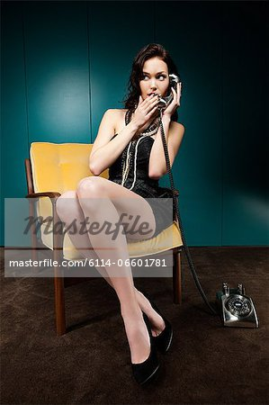 Young woman using vintage telephone Stock Photo - Premium Royalty-Free, Image code: 6114-06601781