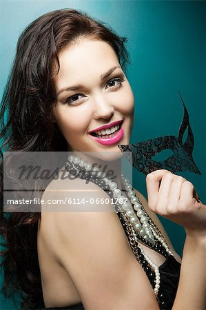 Young woman holding masquerade mask, portrait Stock Photo - Premium Royalty-Free, Image code: 6114-06601787