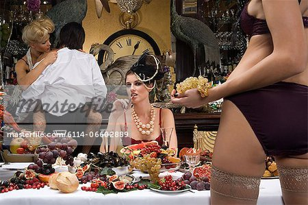 Four people enjoying a banquet Stock Photo - Premium Royalty-Free, Image code: 6114-06602889