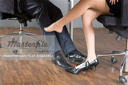 Woman stroking businessmans leg with her foot Stock Photo - Premium Royalty-Free, Image code: 6114-06605855
