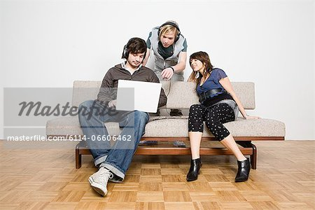 Friends looking at laptop Stock Photo - Premium Royalty-Free, Image code: 6114-06606462
