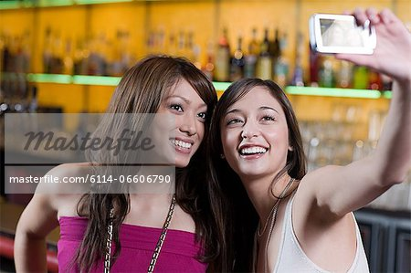Young women taking picture in a bar Stock Photo - Premium Royalty-Free, Image code: 6114-06606790