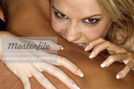Woman biting mans shoulder Stock Photo - Premium Royalty-Free, Image code: 6114-06607317