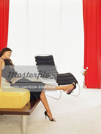 Stylish woman sitting on a bed Stock Photo - Premium Royalty-Free, Image code: 6114-06607524