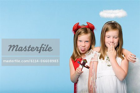 Twin girls dressed as an angel and devil Stock Photo - Premium Royalty-Free, Image code: 6114-06608983