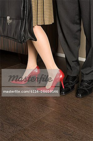 Woman standing on a mans foot Stock Photo - Premium Royalty-Free, Image code: 6114-06609146
