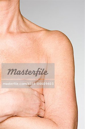 Woman covering her breast Stock Photo - Premium Royalty-Free, Image code: 6114-06609403