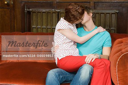 Teenagers kissing on a sofa Stock Photo - Premium Royalty-Free, Image code: 6114-06609853