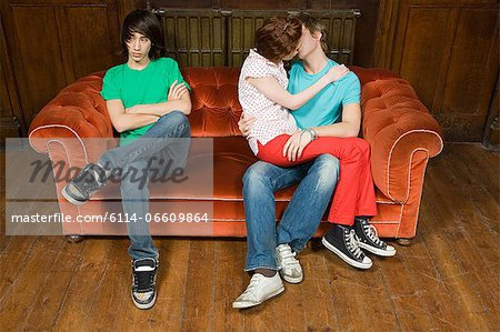 Jealous teenager with kissing couple Stock Photo - Premium Royalty-Free, Image code: 6114-06609864