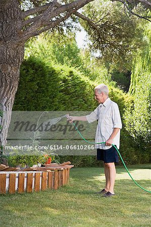 Man watering plants Stock Photo - Premium Royalty-Free, Image code: 6114-06610266