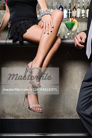 Woman sitting on bar Stock Photo - Premium Royalty-Free, Image code: 6114-06610971