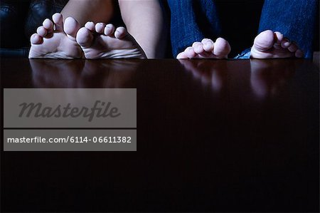 Feet on a table Stock Photo - Premium Royalty-Free, Image code: 6114-06611382