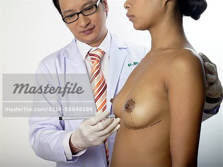 Cosmetic surgeon marking womans breasts Stock Photo - Premium Royalty-Free, Image code: 6114-06646584