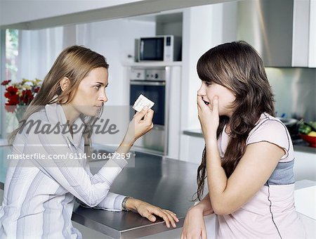 Girl and mother holding condom Stock Photo - Premium Royalty-Free, Image code: 6114-06647259