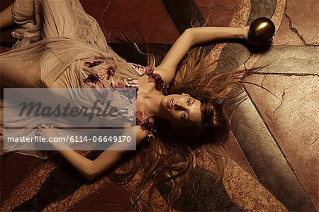 Young woman lying on floor Stock Photo - Premium Royalty-Free, Image code: 6114-06649170