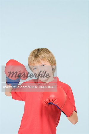 Boy wearing boxing gloves Stock Photo - Premium Royalty-Free, Image code: 6114-06651049