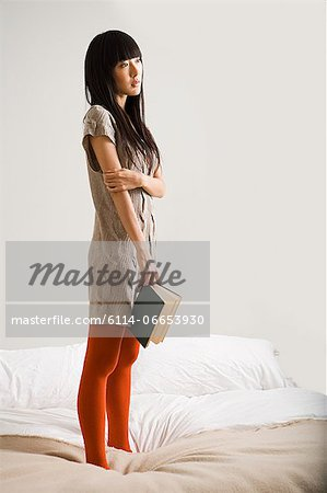 Young woman on bed with book Stock Photo - Premium Royalty-Free, Image code: 6114-06653930