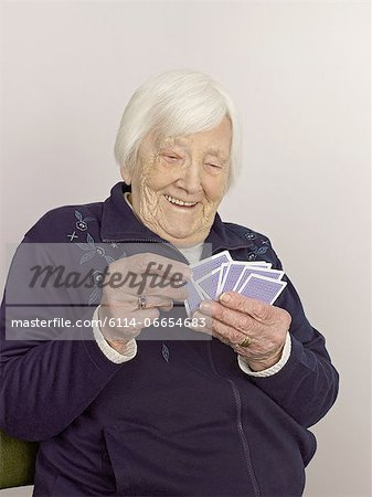 Senior woman with playing cards Stock Photo - Premium Royalty-Free, Image code: 6114-06654683