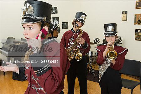 Girl on cellphone in band practice Stock Photo - Premium Royalty-Free, Image code: 6114-06656459