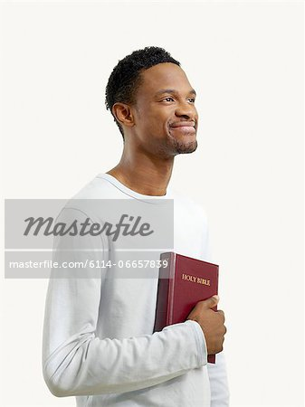 Smiling man holding a bible Stock Photo - Premium Royalty-Free, Image code: 6114-06657839