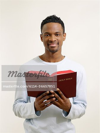 Man holding a bible Stock Photo - Premium Royalty-Free, Image code: 6114-06657851
