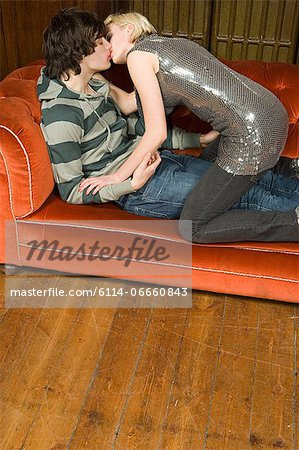 Teenagers kissing on a sofa Stock Photo - Premium Royalty-Free, Image code: 6114-06660843