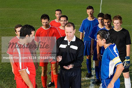 Referee tossing coin Stock Photo - Premium Royalty-Free, Image code: 6114-06660946
