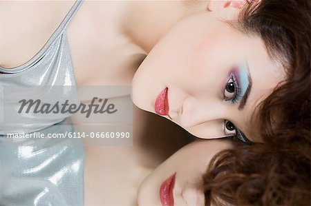 Young woman lying on mirror Stock Photo - Premium Royalty-Free, Image code: 6114-06660990