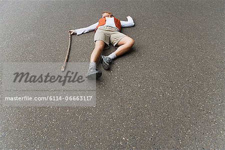 Hiker lying in the road Stock Photo - Premium Royalty-Free, Image code: 6114-06663117