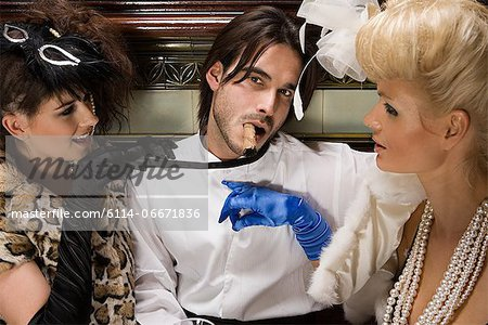 Two lavishly dressed women flirting with a man Stock Photo - Premium Royalty-Free, Image code: 6114-06671836