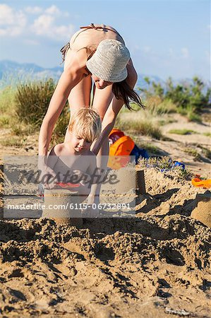 Croatia, Dalmatia, Mother And Son On Beach, Making Sand Cakes Stock Photo - Premium Royalty-Free, Image code: 6115-06732891