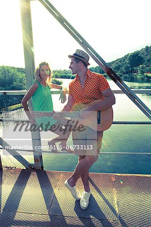 Croatia, Dalmatia, Young couple on a footbridge, man playing guitar Stock Photo - Premium Royalty-Free, Image code: 6115-06733113