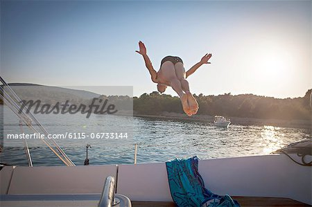 Croatia, Adriatic Sea, Young man diving into water, rear view