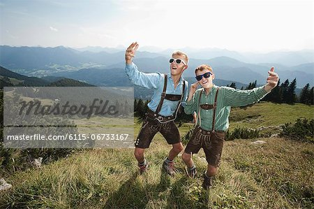 Germany, Bavaria, Two boys in traditional clothing fooling around in mountains Stock Photo - Premium Royalty-Free, Image code: 6115-06733167